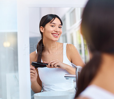 Buy stock photo Shot of a cheerful attractive young woman brushing her hair while looking at her reflection in a mirror at home during the day