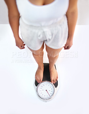 Buy stock photo High angle view of an unrecognizable woman standing on a scale to see her weight