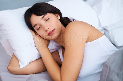 Buy stock photo Shot of a tired attractive young woman sleeping in her bed at home in the morning