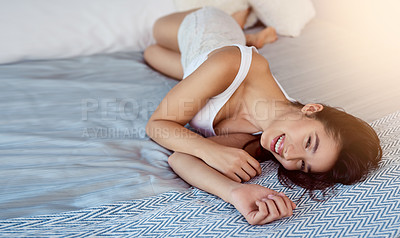 Buy stock photo Shot of a cheerful attractive young woman relaxing in her bed at home in the morning