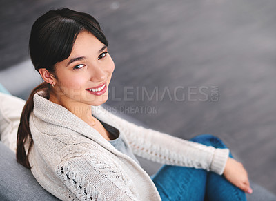 Buy stock photo Portrait of a cheerful young woman seated on a sofa while looking back at the camera at home during the day