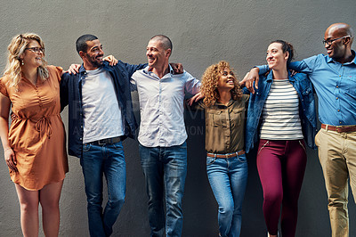 Buy stock photo Shot of a group of people standing together against a wall outside
