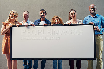 Buy stock photo Portrait of a group of people holding a blank sign against a wall outside