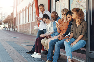 Buy stock photo Shot of a group of people using their cellphones while sitting at a bus stop in the city