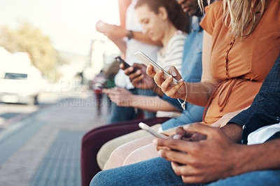 Buy stock photo Closeup shot of a group of people using their cellphones while sitting at a bus stop in the city