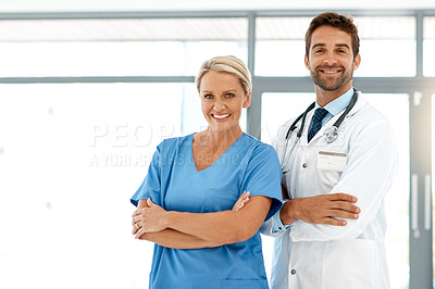 Buy stock photo Cropped portrait of two happy healthcare practitioners standing with their arms folded in the hospital