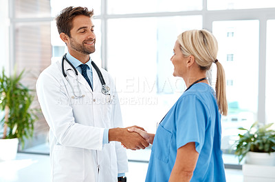 Buy stock photo Cropped shot of two healthcare practitioners shaking hands in the hospital foyer