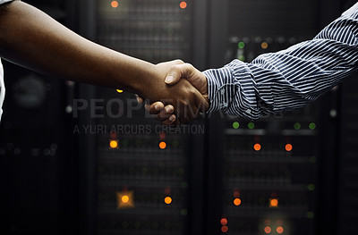 Buy stock photo Cropped shot of two unrecognizable men shaking hands in front of a server in a data center