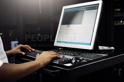 Buy stock photo Cropped shot of an unrecognizable IT technician using a computer while working in a data center