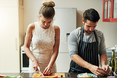 Buy stock photo Cropped shot of an affectionate young couple preparing food together at home