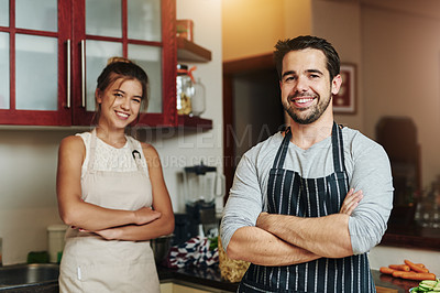 Buy stock photo Cropped portrait of a young couple standing with their arms folded and smiling in the kitchen