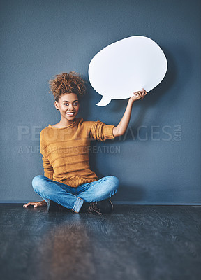 Buy stock photo Studio shot of a young woman holding a speech bubble against a grey background