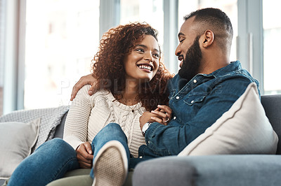 Buy stock photo Shot of a young couple relaxing together on a sofa at home