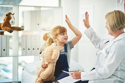 Buy stock photo Shot of an adorable little girl giving her doctor a high five during a checkup