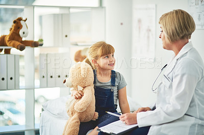 Buy stock photo Shot of a doctor having a consultation with an adorable little girl in her consulting room