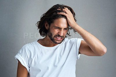 Buy stock photo Studio shot of a young man looking frustrated against a grey background