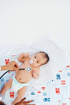 Buy stock photo Shot of an adorable baby boy getting examined with a stethoscope during a checkup with a doctor