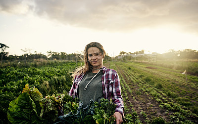 Buy stock photo Shot of a young woman holding a crate of freshly picked produce on a farm