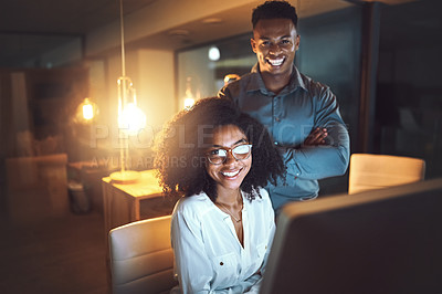 Buy stock photo Portrait of two businesspeople working together on a computer in an office at night