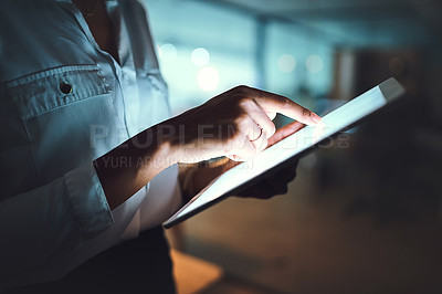 Buy stock photo Closeup shot of an unrecognizable businesswoman using a digital tablet in an office at night