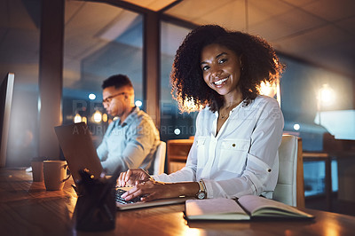 Buy stock photo Portrait of a young businesswoman working on a laptop alongside her colleague in an office at night