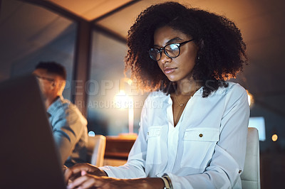 Buy stock photo Shot of a young businesswoman working on a laptop alongside her colleague in an office at night