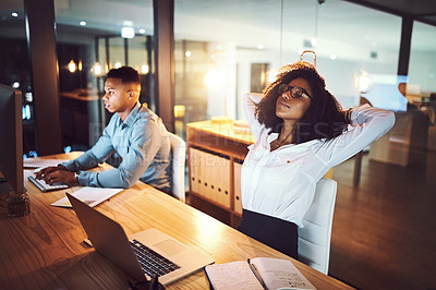 Buy stock photo Shot of a young businesswoman relaxing at her desk while working alongside her colleague in an office at night