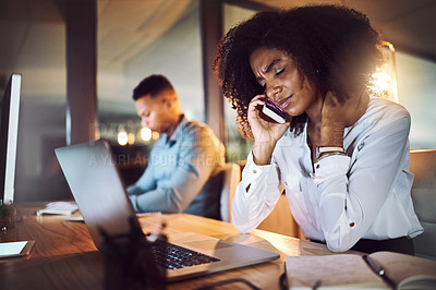 Buy stock photo Shot of a young businesswoman looking stressed out while talking on a cellphone in an office at night