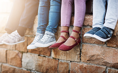 Buy stock photo Cropped shot of unrecognizable elementary school kids sitting on a brick wall outside