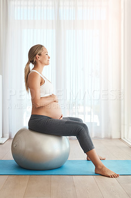 Buy stock photo Shot of a pregnant woman working out with an exercise ball at home