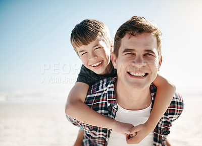 Buy stock photo Shot of a father and his young son enjoying a piggyback ride at the beach