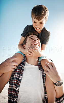 Buy stock photo Shot of a father carrying his young son on his shoulders on a sunny day at the beach