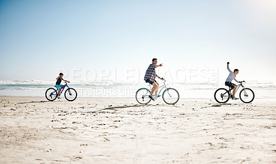 Buy stock photo Shot of a father and his young sons riding bicycles together along the beach