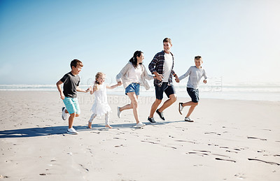 Buy stock photo Shot of a happy young family of five running together on the beach