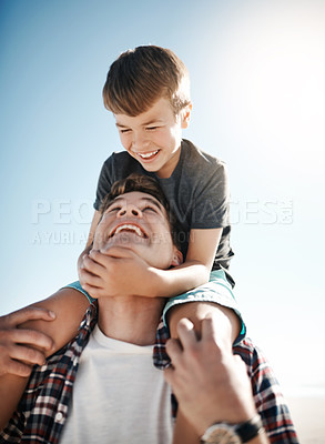 Buy stock photo Shot of a father carrying his young son on his shoulders on a sunny day outdoors