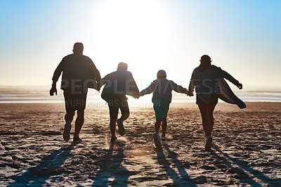 Buy stock photo Rearview shot of a happy young family running together on the beach