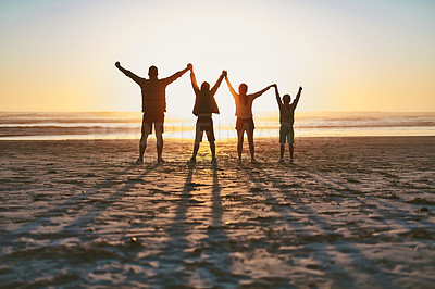 Buy stock photo Rearview shot of a happy young family having fun together on the beach at sunset