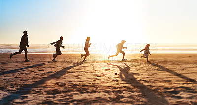 Buy stock photo Shot of a happy young family running together on the beach
