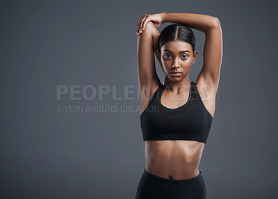 Buy stock photo Studio portrait of a sporty young woman stretching her arms against a grey background