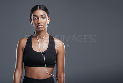 Buy stock photo Studio portrait of a sporty young woman listening to music against a grey background