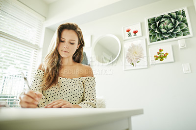 Buy stock photo Shot of a young woman going through paperwork in her study at home