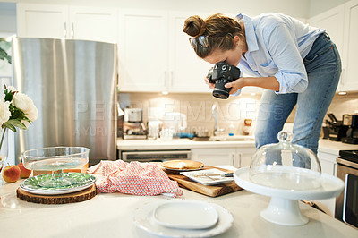 Buy stock photo Shot of a young woman using a camera to take a picture of the pie she's baked at home