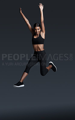 Buy stock photo Full length studio portrait of a young sportswoman jumping high in the air against a gray background