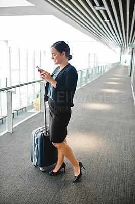Buy stock photo High angle shot of an attractive young businesswoman sending a text message while standing in the airport