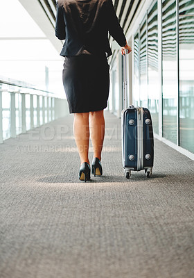 Buy stock photo Rearview shot of an unrecognizable young businesswoman wheeling her luggage through the airport