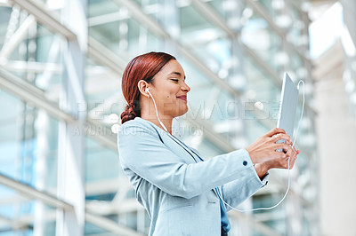 Buy stock photo Cropped shot of an attractive young businesswoman using her tablet while standing in the airport