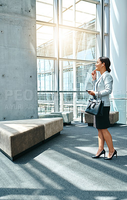 Buy stock photo Full length shot of an attractive young businesswoman making a phonecall while walking through the airport
