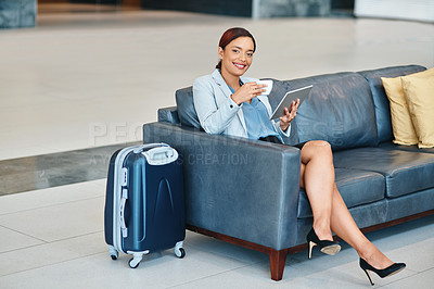 Buy stock photo High angle portrait of an attractive young businesswoman using her tablet while sitting in the airport