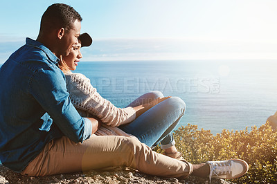 Buy stock photo Shot of a happy young couple sitting on a rock and enjoying the ocean view
