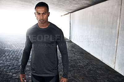 Buy stock photo Cropped portrait of a handsome and athletic young man standing outside while running in the city
